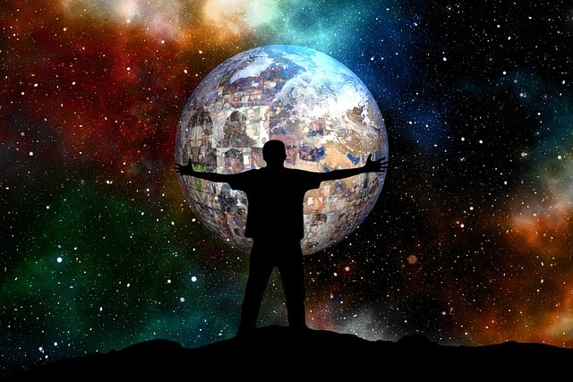 Man standing in front of the globe on a star lighten night.